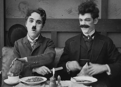 Austin and Chaplin with a different meal in The Immigrant